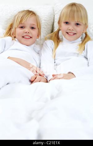 Porträt von zwei süßen Schwestern im Bett liegend - Stockfoto