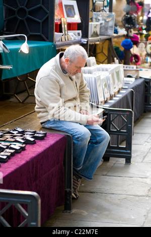 Covent Garden, langweilig grau oder grau dunkelhaarigen Mann, Standinhaber sitzend mit Handy oder Handy, wartet - Stockfoto