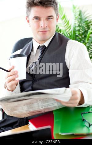 Ernsthaften Geschäftsmann, trinken einen Kaffee beim Lesen einer Zeitungs - Stockfoto