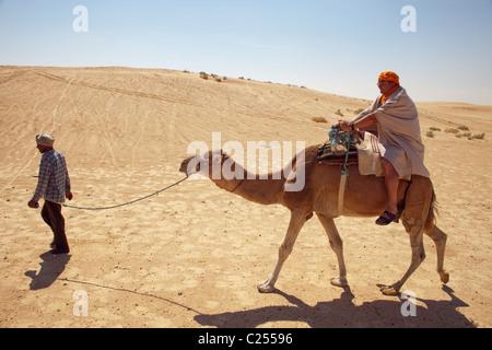 Touristen, die Einnahme von einem Kamel reiten in der Nähe von Douz, Tunis, Nordafrika - Stockfoto