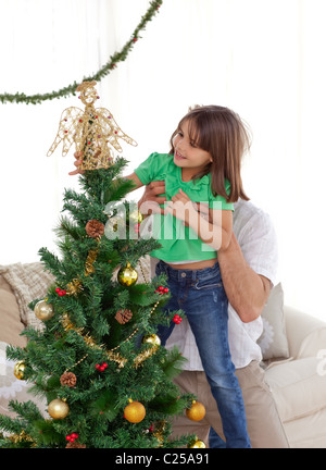 Aufmerksamen Vater hält ihre Tochter um den Weihnachtsbaum schmücken - Stockfoto