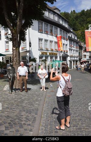 Touristen fotografieren durch eine Statue eines alten Mannes im Zentrum von Monschau, Aachen, Nordrhein-Westfalen, - Stockfoto