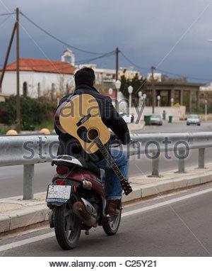 Mann mit Motorrad ohne Helm mit Gitarre - Stockfoto
