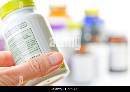 Hand, die Medizin-Flasche, Etikett lesen - Stockfoto