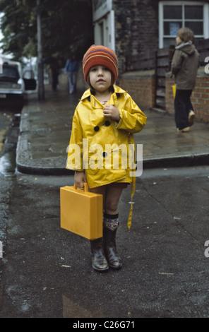 junge Mädchen tragen gelben Regenmantel halten ihre gelben Kunststoff Schule Schulranzen und Gummi-Stiefel - Stockfoto
