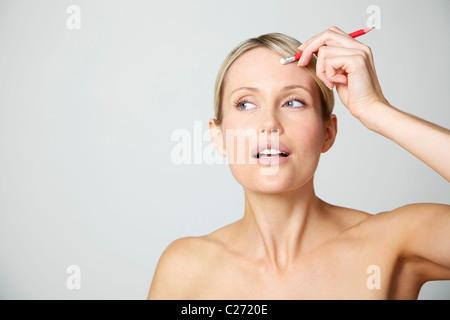 Frau Holding Bleistift gegen die Stirn - Stockfoto