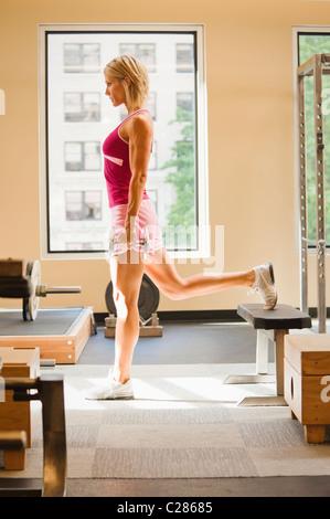 Eine Frau tut einem vierbeinigen Hantel Kniebeugen / stürzt sich in ein Fitnessstudio. - Stockfoto