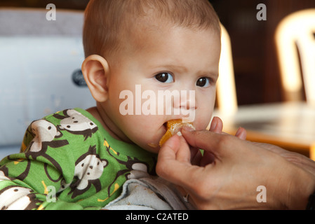 Babymädchen gefüttert eine Orangenscheibe - Stockfoto