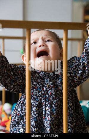 Babymädchen weint in Krippe - Stockfoto