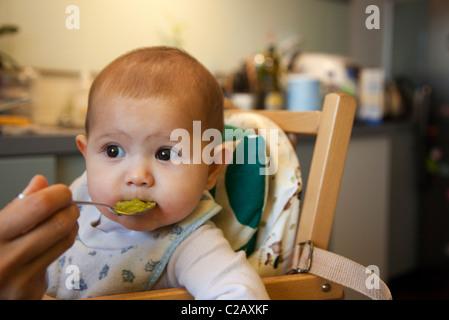 Babymädchen gefüttert im Hochstuhl - Stockfoto