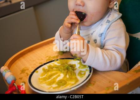 Babymädchen kauen auf Löffel - Stockfoto