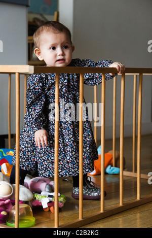Babymädchen stehen im Laufstall - Stockfoto