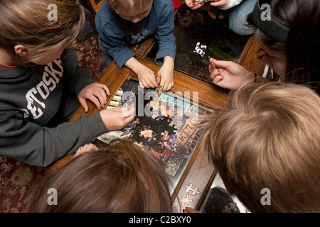 Sechs Kinder Alter 4 bis 15 arbeiten auf Jigsaw Puzzle. St Paul Minnesota MN USA - Stockfoto