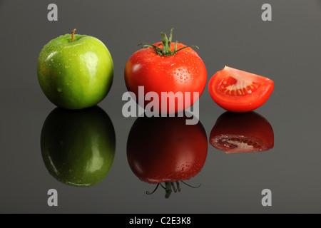 Grüner Apfel und Tomaten auf einer reflektierenden Oberfläche - Stockfoto