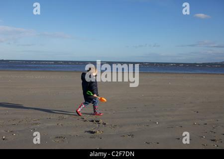 Kleiner Junge mit einer roten Eimer und gelbe Schaufel Strandläufer und auf der Suche nach Muscheln - Stockfoto