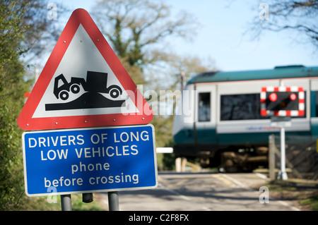 Warnzeichen für LKW-Fahrer von niedrigen langen Fahrzeuge nähert sich eine ländliche Bahnübergang, Suffolk, England. - Stockfoto