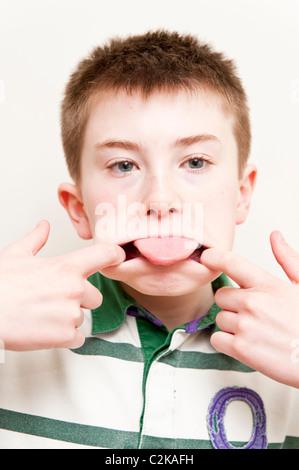 Ein MODEL Release Bild eines elfjährigen Jungen ziehen ein lustiges Gesicht im Innenbereich - Stockfoto