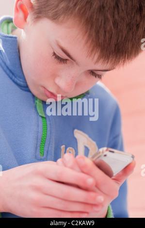 Ein MODEL Release Bild eines elf Jahre alten Jungen mit seinem Ipod Touch im Innenbereich - Stockfoto