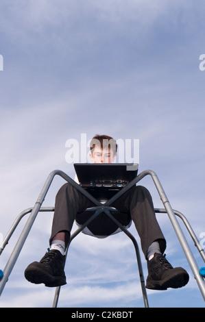 Ein MODEL Release Bild eines elf Jahre alten Jungen mit seinem Laptop im Freien auf einem Klettergerüst im Vereinigten - Stockfoto