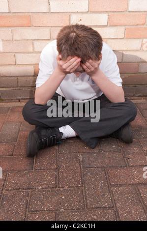 Ein MODEL Release Bild eines elf Jahre alten Jungen auf der Suche deprimiert im Freien tragen seine Schuluniform - Stockfoto