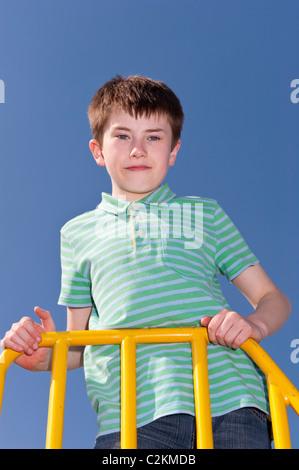 Ein MODEL Release Bild eines elfjährigen Jungen im Freien auf einem Klettergerüst im Vereinigten Königreich - Stockfoto