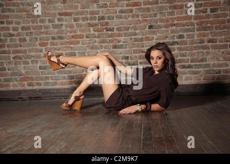 Ziemlich kaukasischen Frau liegend auf Holzboden mit Wand hinter - Stockfoto