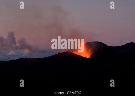 Lava vom Vulkan Eyjafjallajokull spuckender, Silhouette, gegen Sonnenuntergang, Southern Island - Stockfoto