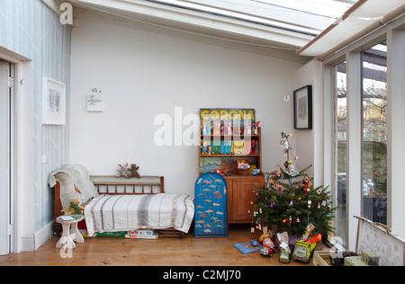 Weihnachtsbaum im Wintergarten Spielzimmer mit Spielsachen und Vintage-Möbel - Stockfoto