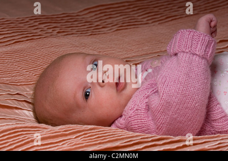 drei Monate altes Baby Mädchen trägt rosa Strickjacke rosa Bettdecke liegend - Stockfoto