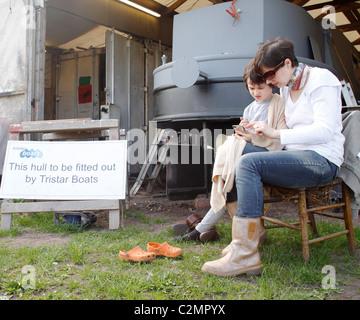 Ein kleiner Junge spielt mit seiner Mutter Handy an einem Bootshaus. - Stockfoto