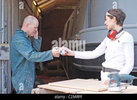 Mann und Frau eine Pause von Arbeiten für den Bau eines Bootes, eine Tasse Tee trinken und am Telefon zu sprechen. - Stockfoto