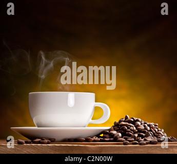 Tasse Kaffee mit Kaffeebohnen auf einem schönen braunen Hintergrund. Stockfoto