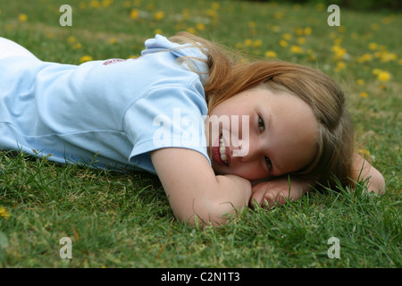 Teenager-Mädchen entspannend auf Wiese Feld und glücklich lächelnd in Richtung der Kamera. - Stockfoto