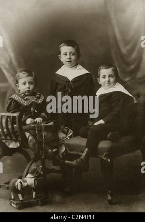 Studio-Porträt von drei elegant gekleidet viktorianischen jungen in Sailor Anzügen mit einem Holzpferd Spielzeug - Stockfoto