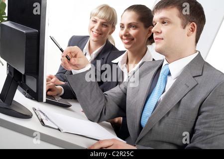 Porträt von freundlichen workteam.20.We Blick auf beim zuversichtlich Geschäftsmann zeigte auf Bildschirm - Stockfoto