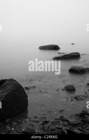 Steinen im Meer gesehen mit Nebel bedeckt - Stockfoto