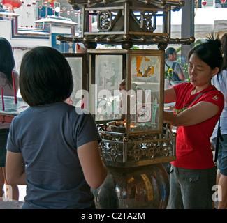 Einheimischen Mädchen Kerzen, Cheng Hoon Teng chinesischen Tempel, Malacca, Provinz von Malacca, Malaysia. - Stockfoto