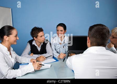 Gruppe von Geschäftsleuten, die mit einem Laptop bei einem Treffen, sie haben Spaß und Diskussion zusammen - Stockfoto
