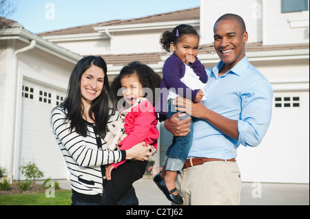 Stolze Eltern und Tochter stehen in Einfahrt - Stockfoto