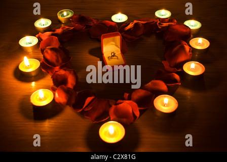 Diamant-Ring in einer Box in der Mitte ein Herz mit Rosen und Kerzen leuchten Blütenblätter - Stockfoto