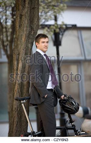 Ein Geschäftsmann mit seinem Fahrrad stehen - Stockfoto