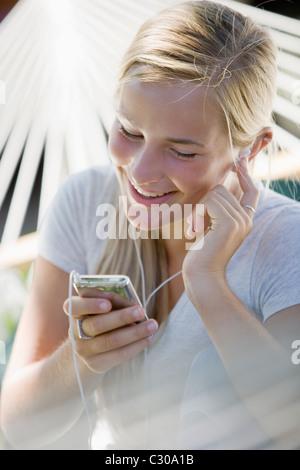 Teenager mit Ohrhörer anhören von MP3-player - Stockfoto