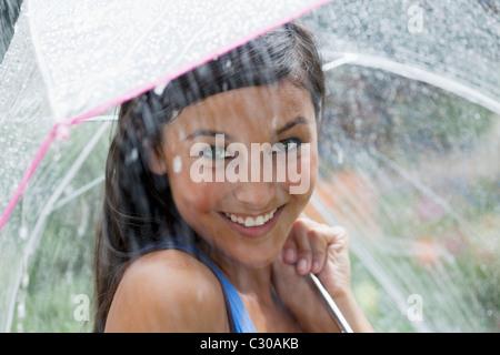 Schöne junge Frau lächelt in die Kamera halten Sie einen Regenschirm unter einem Wasserstrahl. Horizontalen Schuss. - Stockfoto