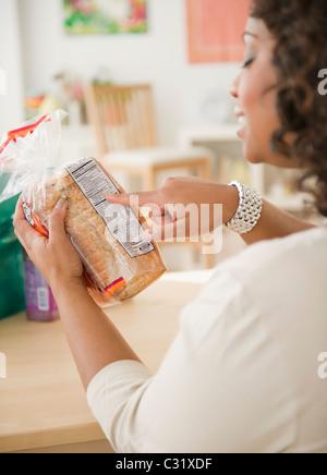 Afroamerikanische Frau betrachten Laib Brot - Stockfoto