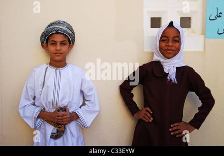 Oman, Maskat, Porträt einer Schulmädchen und ein Junge in traditioneller Kleidung - Stockfoto