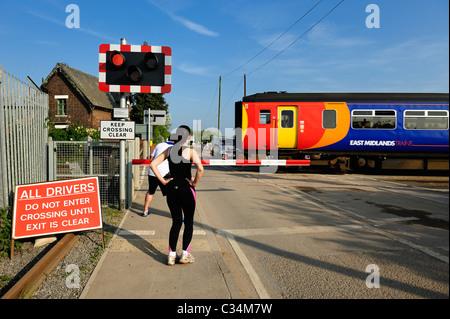 Jogger am ein Bahnübergang warten, während eine lokale s-Bahn Beeston Nottingham England uk verläuft - Stockfoto