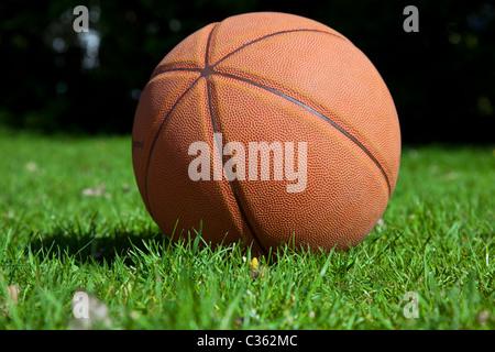 Basketball im Park auf dem Rasen liegen gelassen - Stockfoto