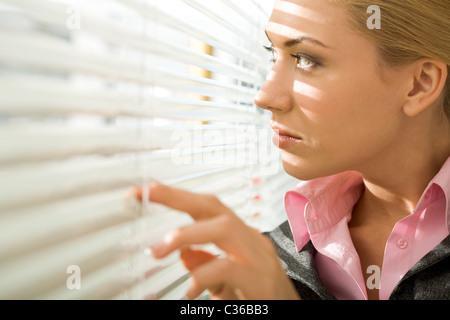 Bild hübsche Geschäftsfrau Durchsicht Jalousie im Büro - Stockfoto