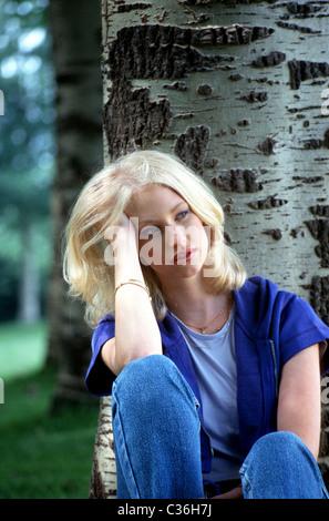 Unglückliche junge Frau lehnte sich gegen Baum im Park neben umgekippt und Kontemplation mit Kopf in den Händen - Stockfoto