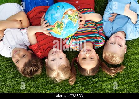 Gruppe von glücklichen Kindern liegen auf einer grünen Wiese mit Globus - Stockfoto
